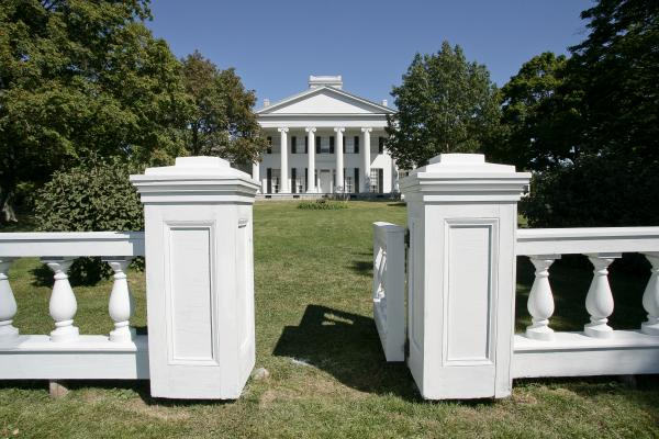 white-columned-building-viewed-across-a-lawn-from-a-gate