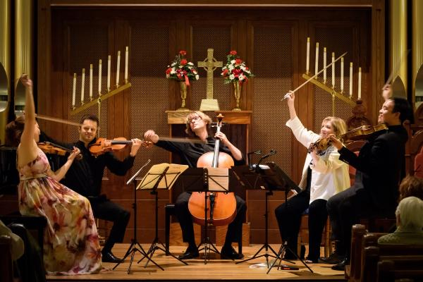Geneva Music Festival artists performing with bows raised