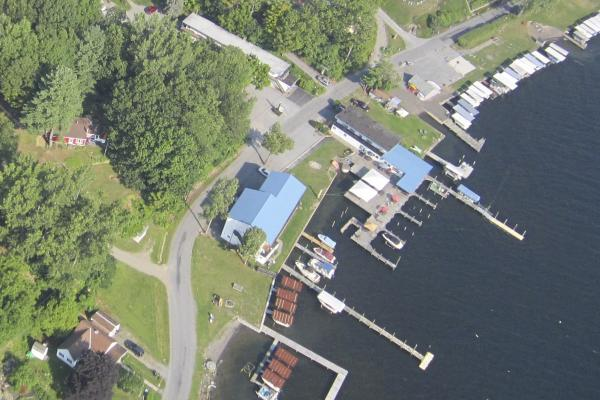 aerial of property with blue roof, docks, boats in slips