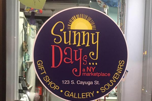 Sunny Days of Ithaca door front with circle sticker purple background yellow sun above sunny days text