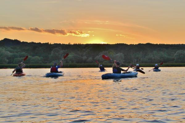Kayaks on Keuka Lake in the evening with setting sun.