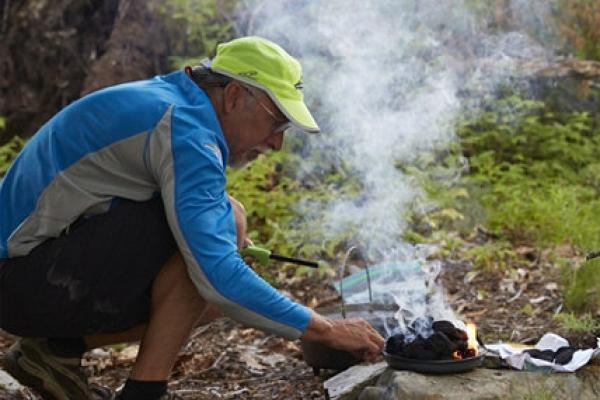 Person cooking over a campfire.