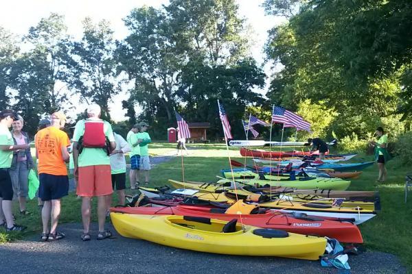 Photo of people gathered next to kayaks.
