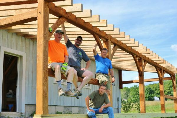 Men sitting on Timber Frame structure.