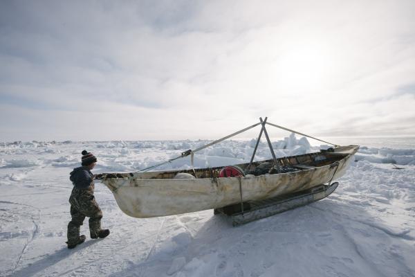 Man pushing boat on ice