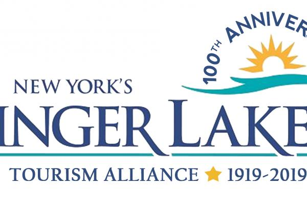 finger lakes tourism alliance dark blue and teal text with teal swish at top left, yellow sun outline and dark blue 100th Anniversary text in semi circle on top of sun