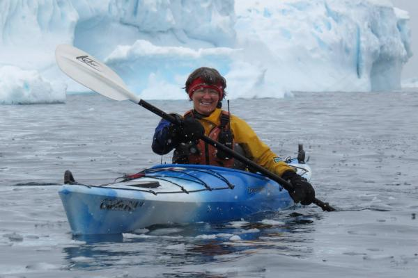 Louise Adie displays a wide grin from her kayak's seat. in front of glaciers.