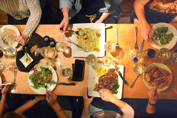 people at table with image from over table of plates and food on plates, wineglasses on table filled with wine