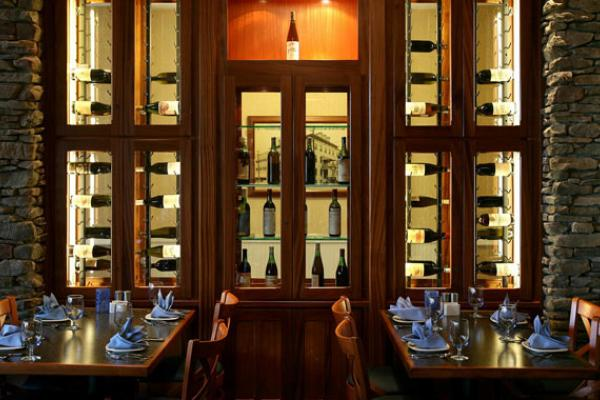 lighted wine rack display with wine bottles on their sides and dining tables with settings and naples in the foreground