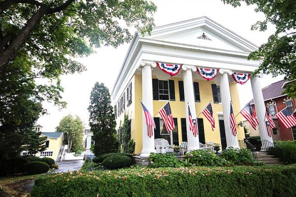 front exterior image with yellow walls, white columns and 3 American flags hanging from columns
