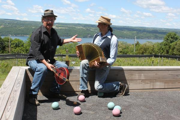 two men in hats sitting on bocce court railing overlooking Seneca Lake looking at one another and the view and smiling