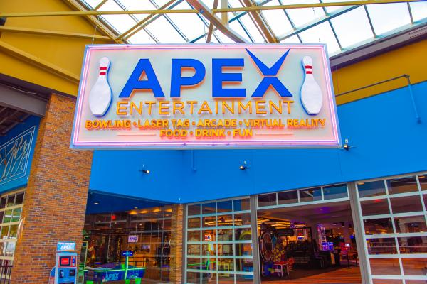 apex blue lettering sign above entrance of venue with lights from games coming through windows looking inside