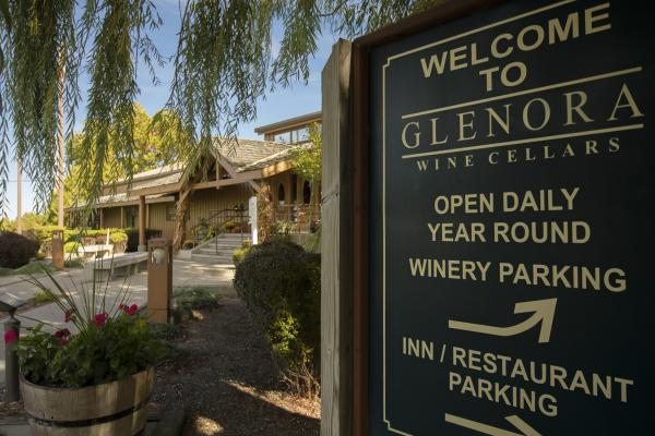 Exterior shot of the front entrance of Glenora Wine Cellars, featuring a sign and willow tree.