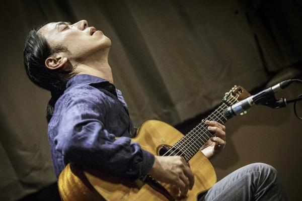 Hiroya Tsukamoto playing acoustic guitar