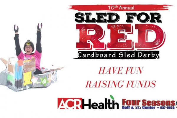 10th Annual sled of red cardboard sled Derby with ACR Health: Girl sledding in cardboard
