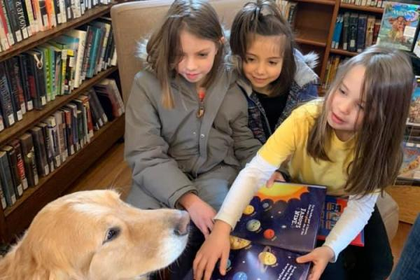 Kids and dog at library reading books