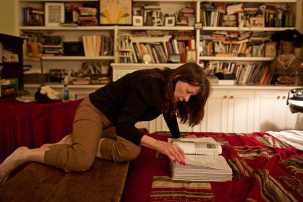 Joanne O'Connor with books in living room