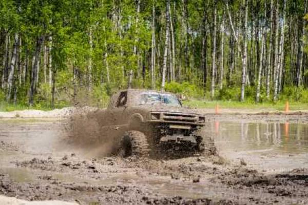 Pick-up truck driving through mud bog