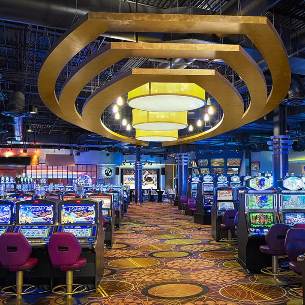 gaming floor with slots and chairs on floor with big light overhead