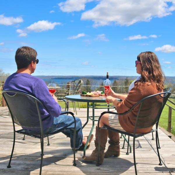 Couple enjoying wine tastings on the Buttonwood Grove deck