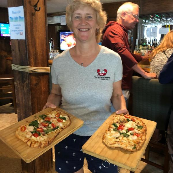 Mary Alice, owner of Beachcomber restaurant, holding 2 flatbread pizzas