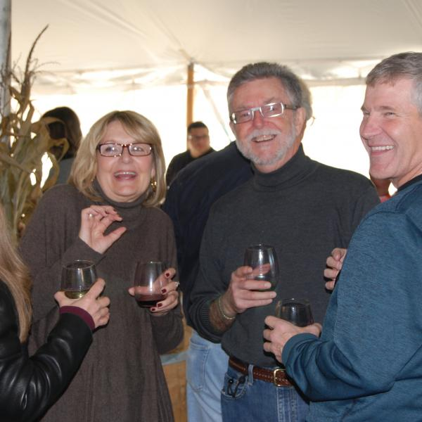 Four adults enjoying a glass of nouveau wine underneath a white tent, with festive decorations.