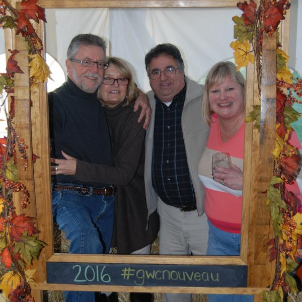 Our winemaker Steve and friends celebrating Nouveau by taking a group photo in a festively decorated photo frame prop.