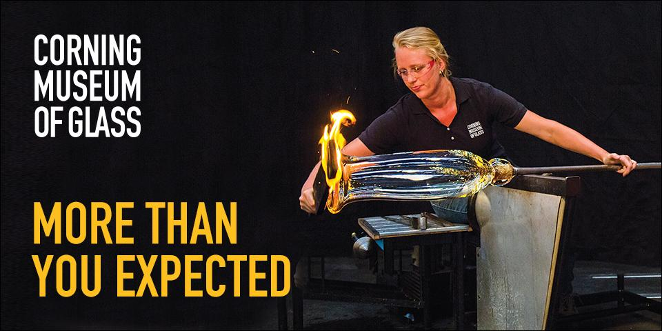 glassworker with glass on bench flame on end of glass and black background yellow and white text