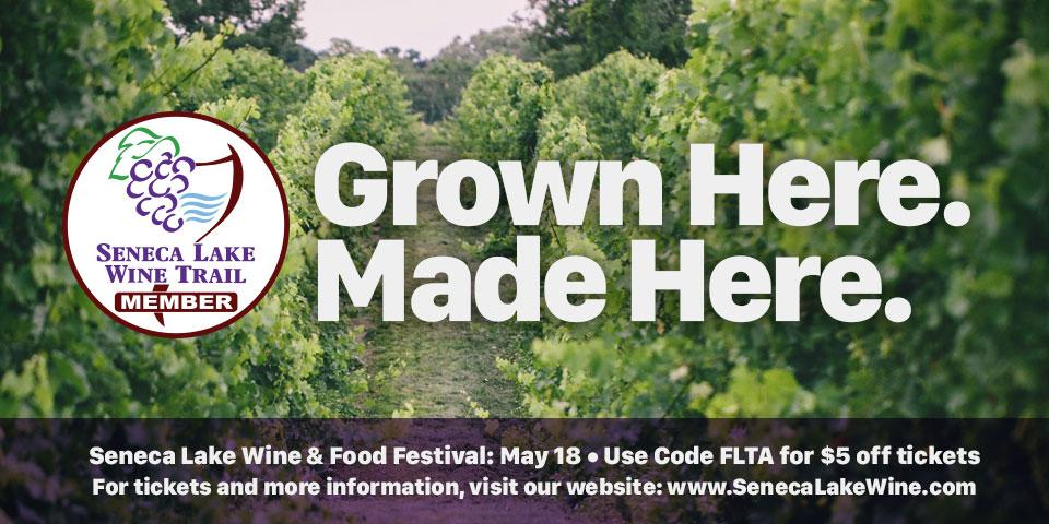 grapevines in background with white circle wine glass and grape clip art logo overlaid. White text overlay with 'Grown Here. Made Here.'